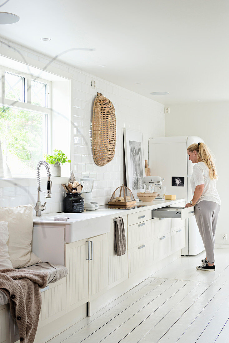Woman standing in front of open drawers in bright country-house kitchen