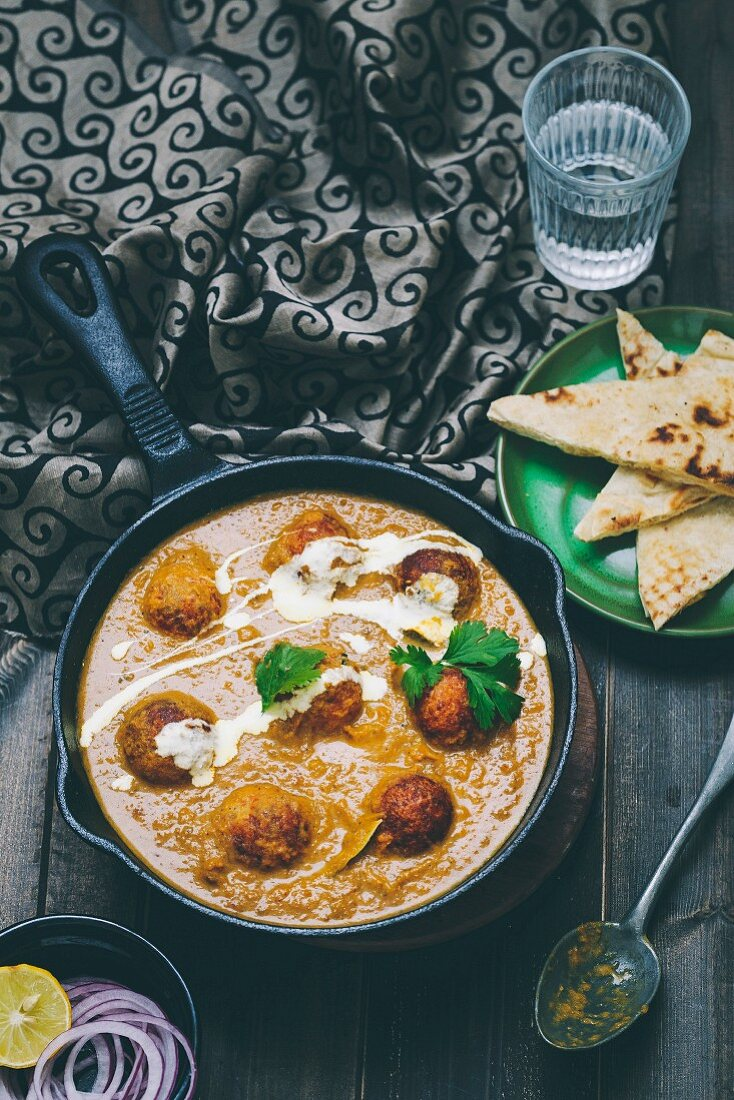 Malai Kofta, a Mughlai Speciality dish with deep fried Potato Paneer Balls simmered in Spiced Onion Tomato Gravy