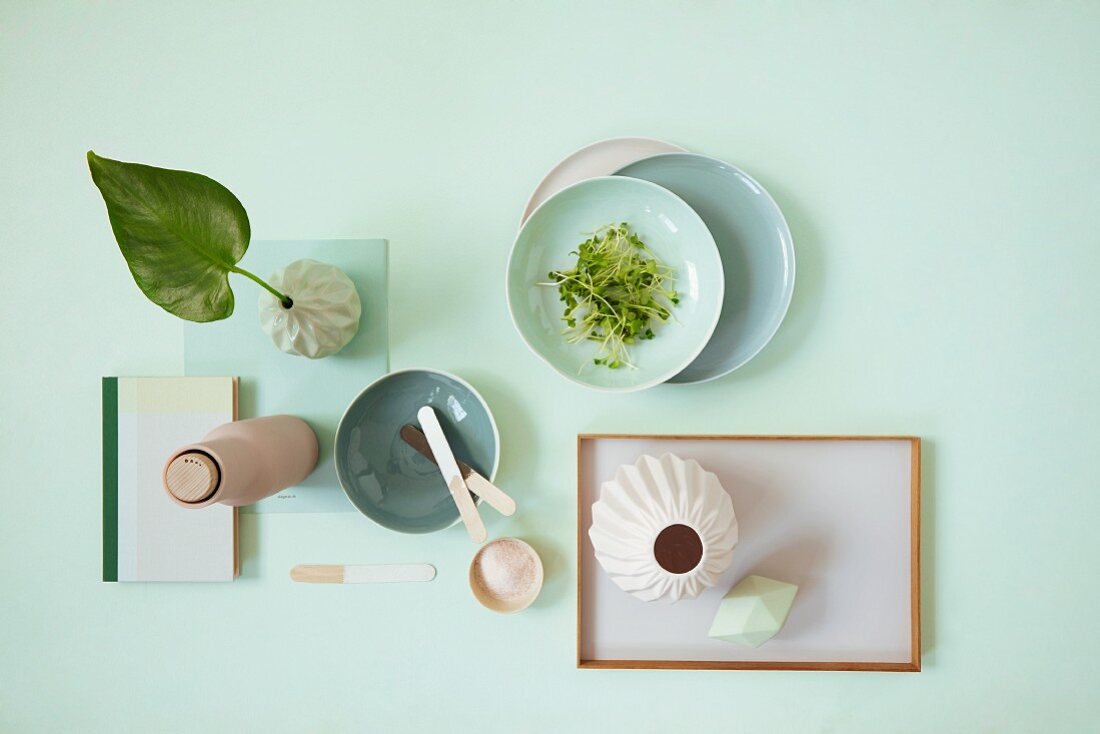 A table laid with a vase, crockery, cress and a tray