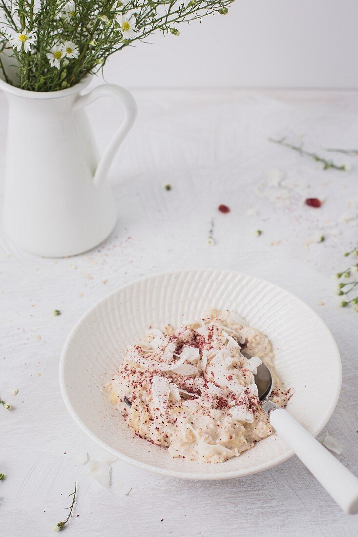 Overnight oats or bircher muesli with coconut and cranberries, and fresh daisies