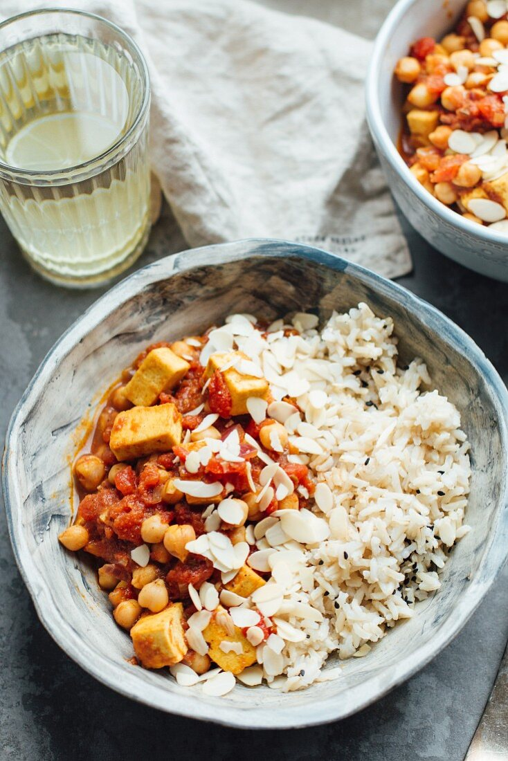 Vegan curry with chickpeas and tofu, served with brown rice and almond flakes