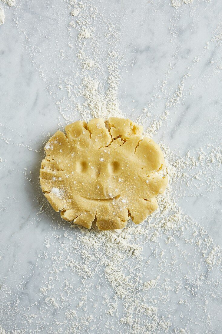 Shortcrust pastry with a face drawn into it on a worktop dusted with flour (seen from above)