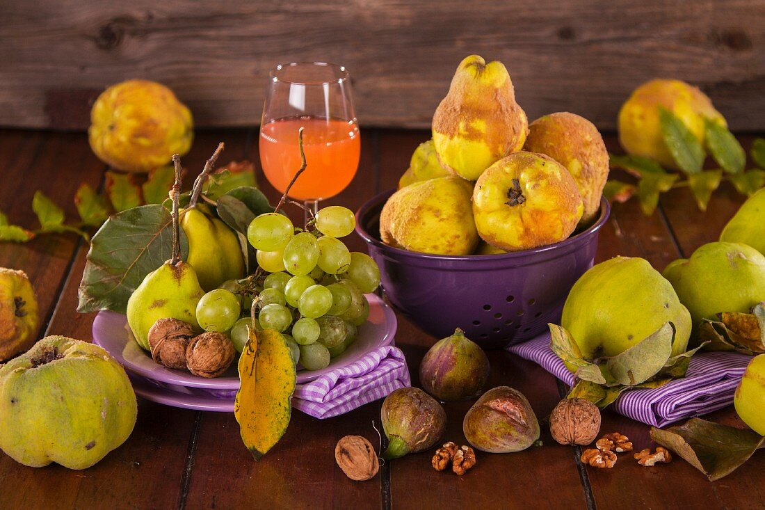 Still life with autumn fruits, quince juice and walnuts
