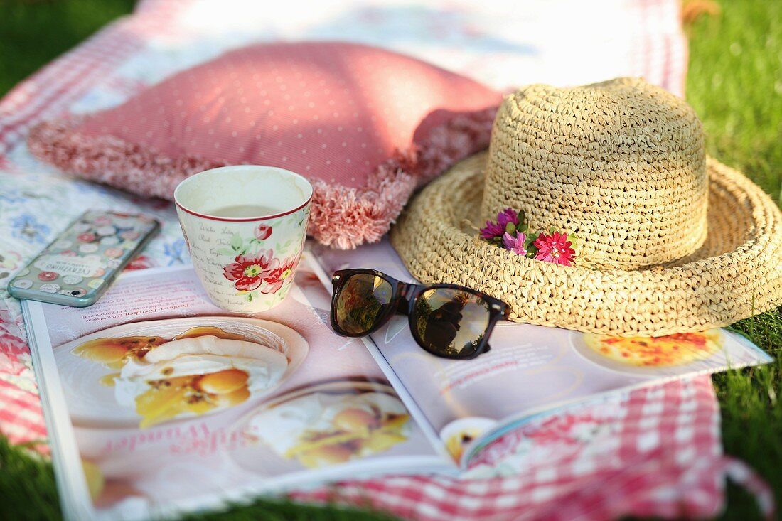 A blanket on the grass, coffe, straw hat and journal