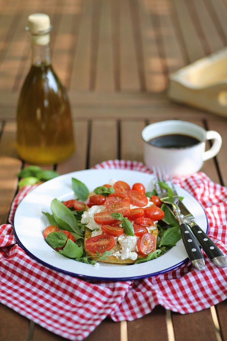 Bruschetta with ricotta cheese, cherry tomatoes and basil served in garden