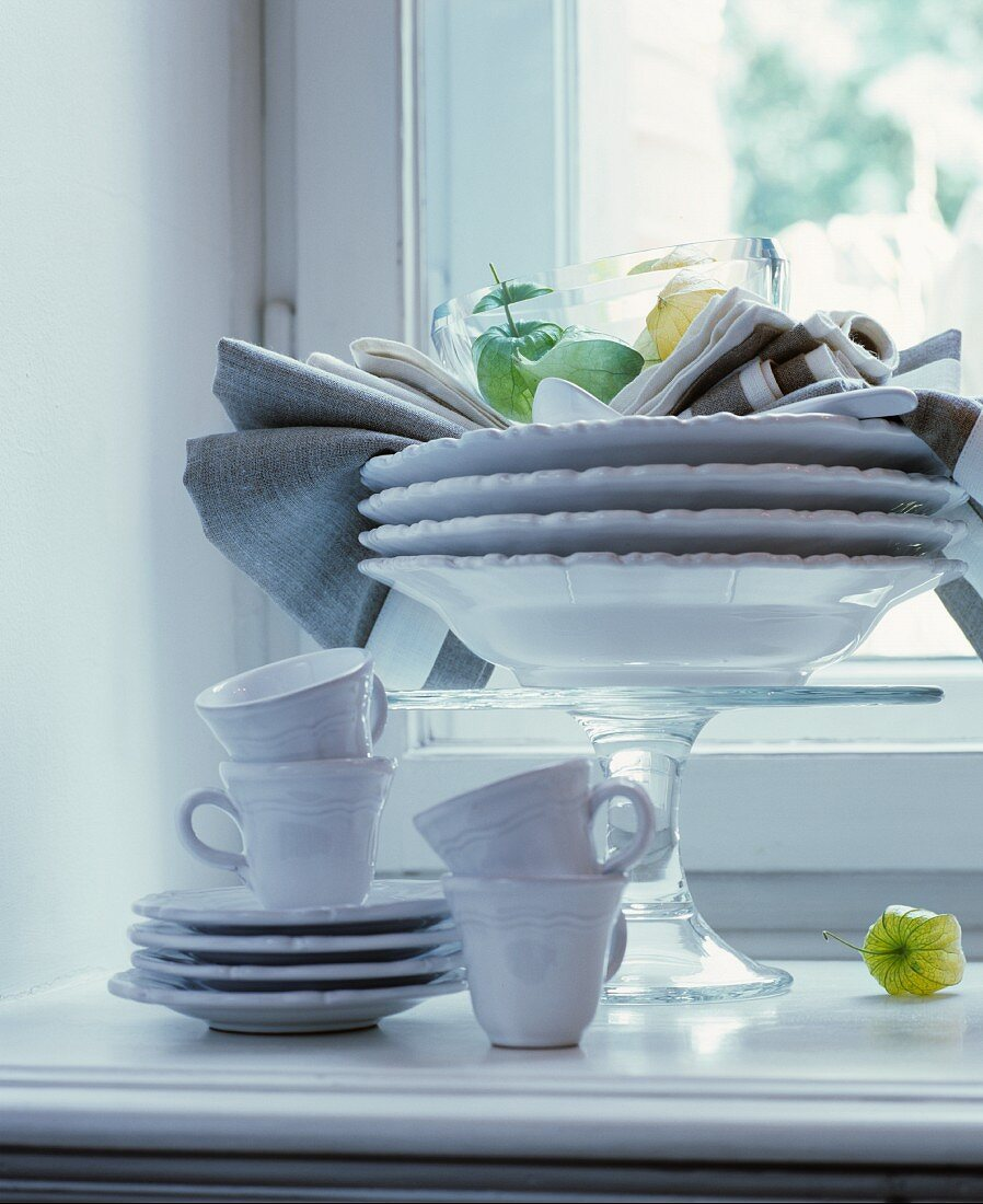 Plates stacked on cake stand and white coffee service on windowsill