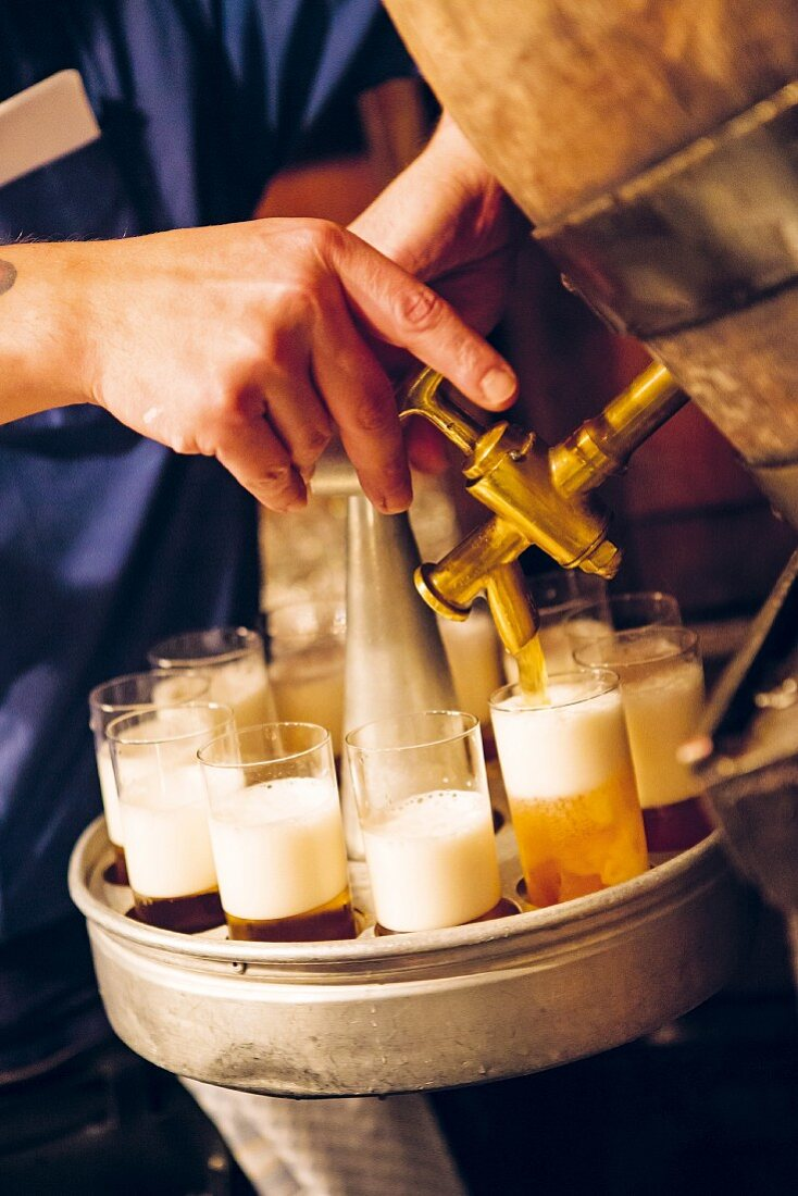 The local Cologne beer Kölsch being tapped from the keg at the 'Lommerzheim' pub and restaurant in Deutz, Cologne, Germany