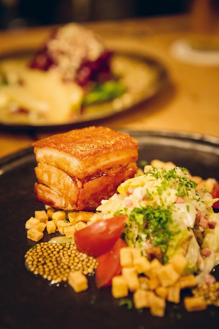 Pork belly and pointed cabbage served at the 'Metzger und Marie' restaurant in Cologne, Germany