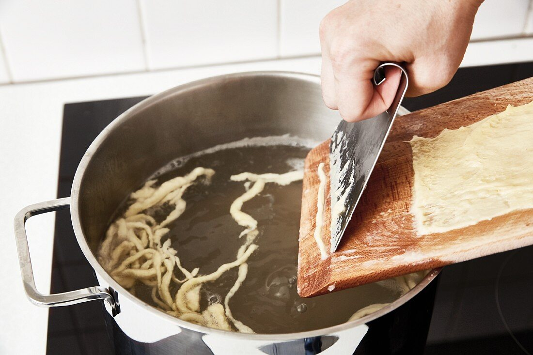 Spaetzle being scraped into boiling water by hand