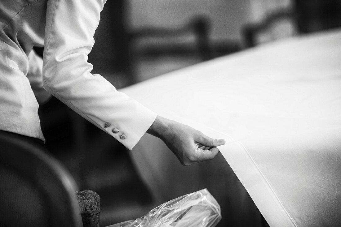 A waiter pulling a tablecloth over a restaurant table