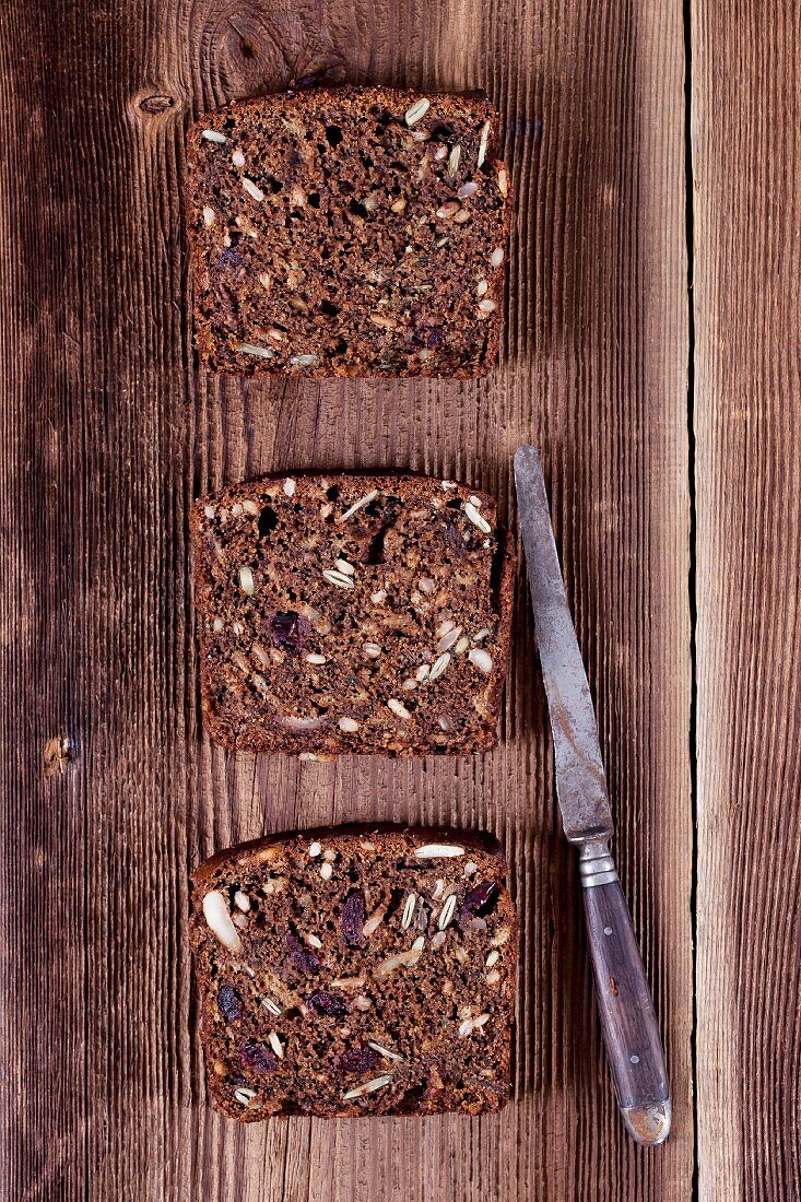 Three slices of banana bread with sunflower seeds, pumpkin seeds, cranberries, apple butter and walnut flour