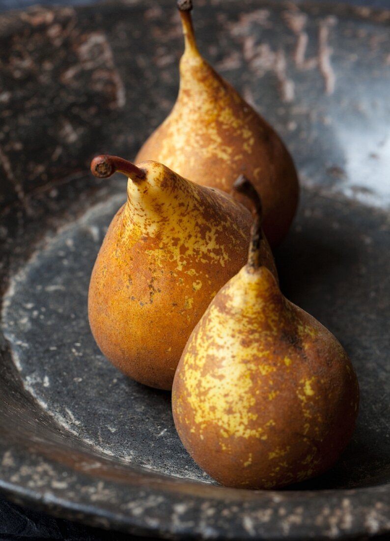 Three organic conference pears in a stone bowl