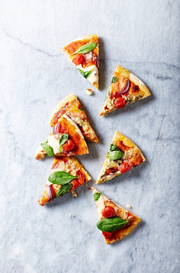 Slices of mozzarella and gorgonzolla pizza with spinach leaves