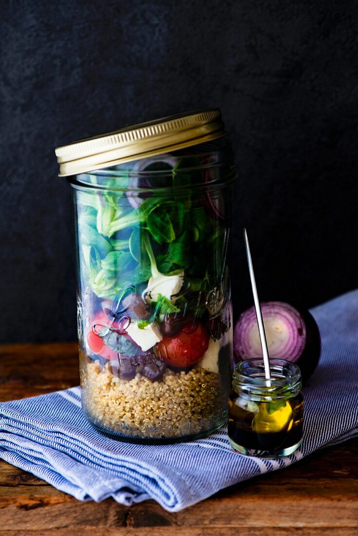 Lunch in a glass jar: quinoa salad, cherry tomatoes, lambs lettuce, black olives and goat's cheese