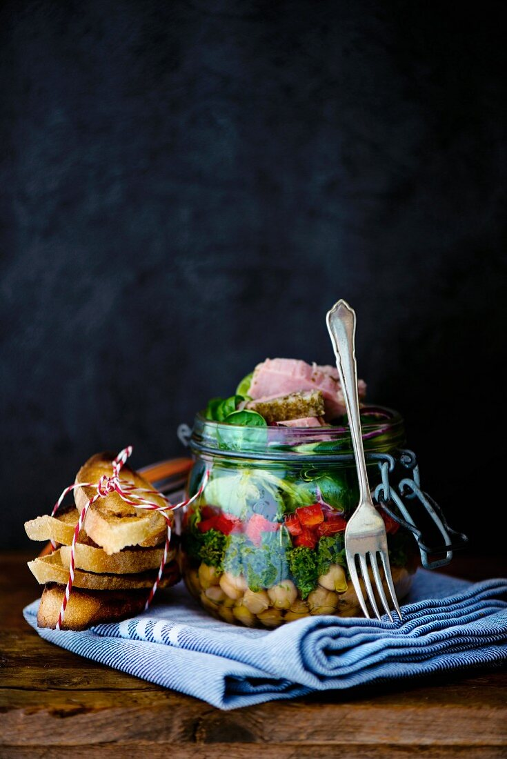Lunch in a glass jar: chickpeas, green cabbage, lambs lettuce, burgundy ham, parsley jelly and toasted bread