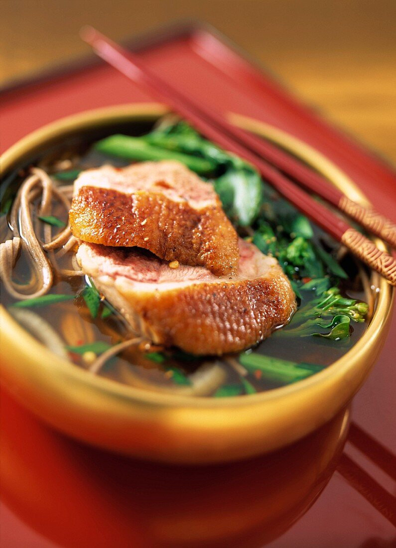 bowl of duck and noodle soup in oriental setting