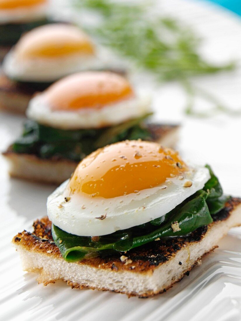 Peppered quails eggs in spinach on an English muffin canapes