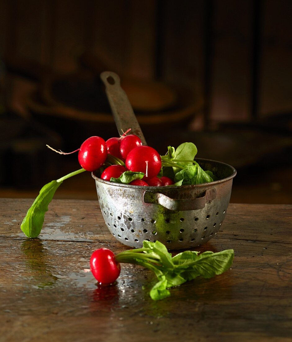 Radishes in and in front of an old kitchen sieve
