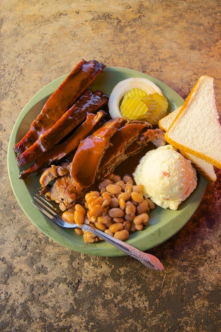Barbecue ribs with beans, mashed poatoes, white bread, onion and pickle cucumber (Texas, USA)