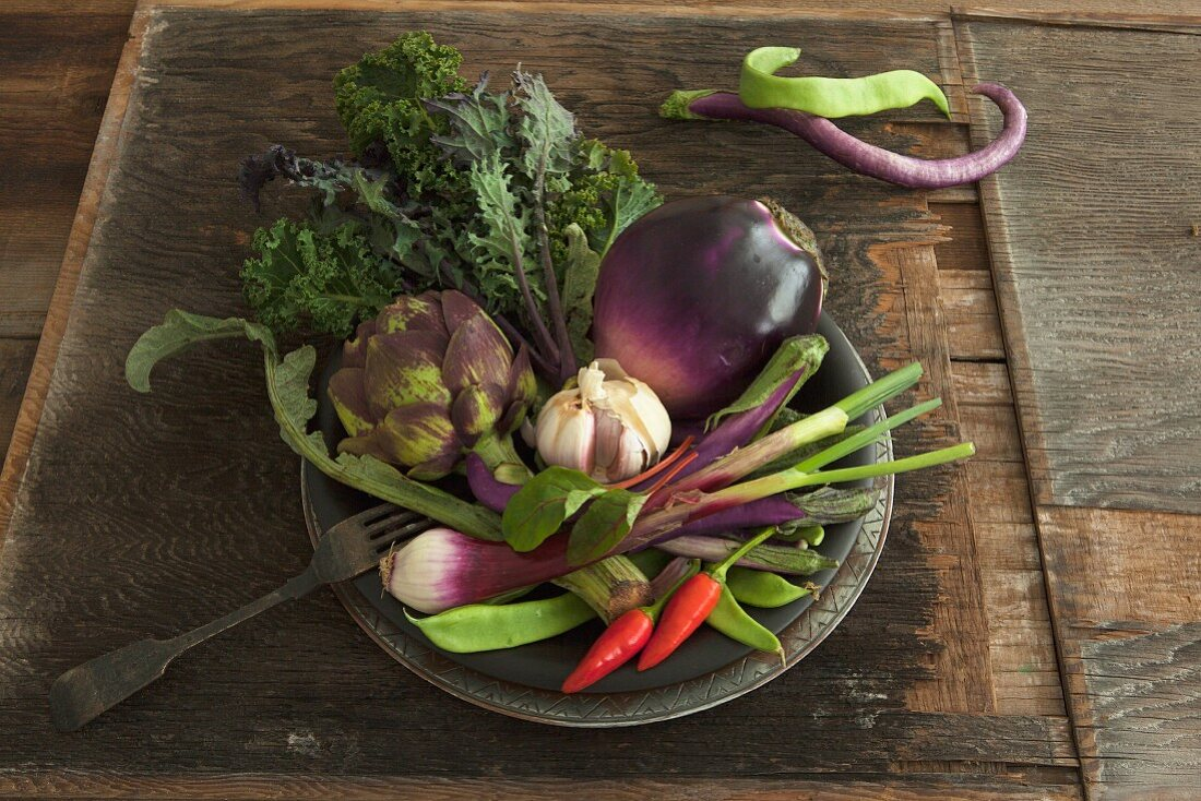 A bowl of vegetables with aubergines, artichoke, garlic and chillies