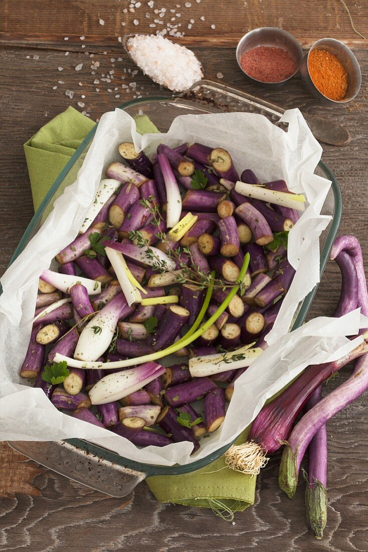 Chopped long, thin aubergines and spring onions in parchment paper