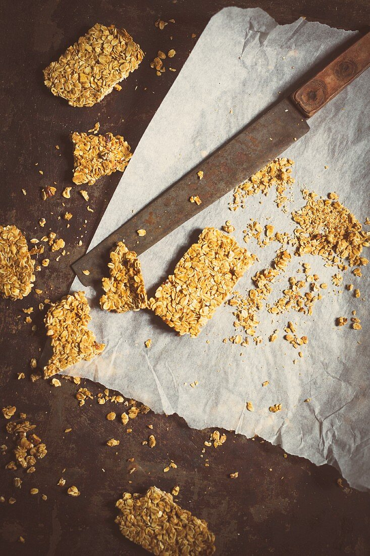 Homemade muesli bars on baking paper with a knife