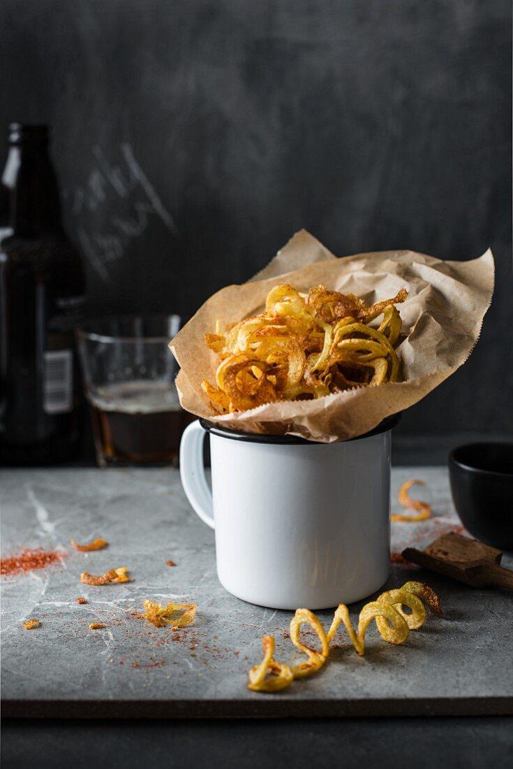 Curly potato fries with smoked paprika in an enamel mug