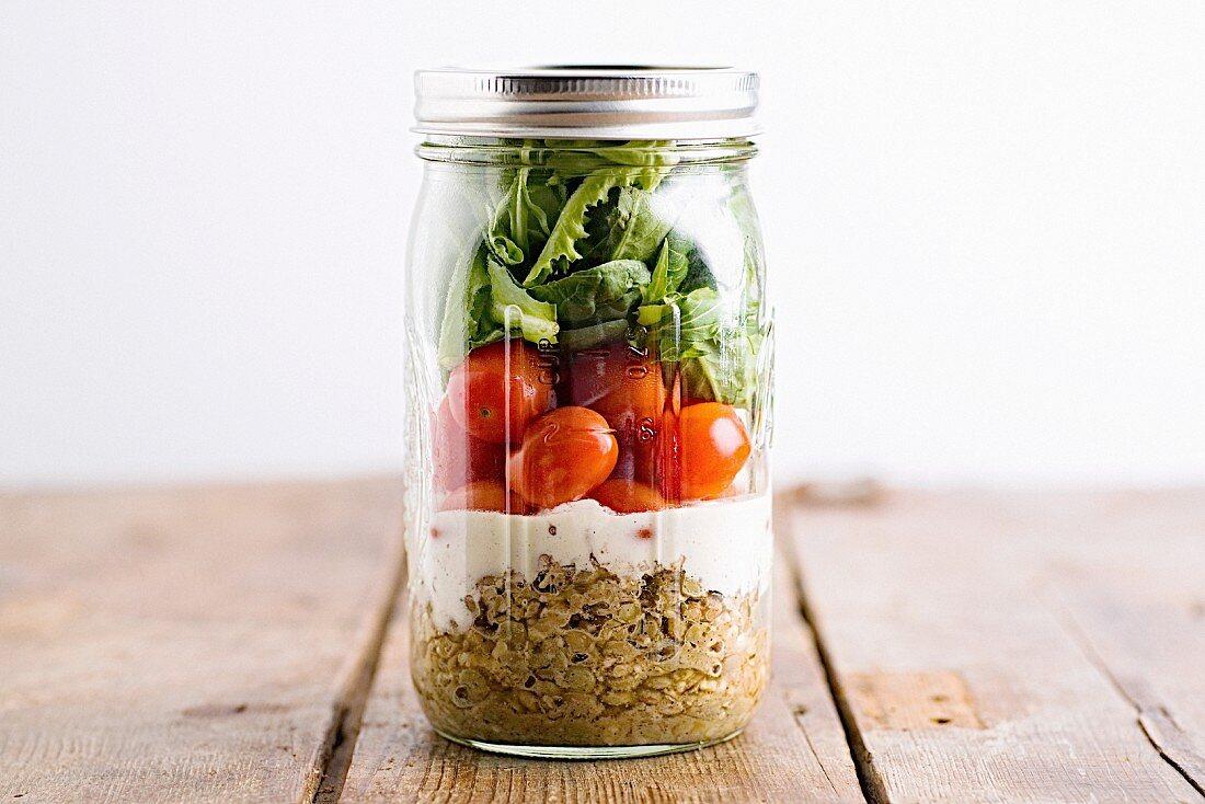 A layered salad in a screw top glass jar