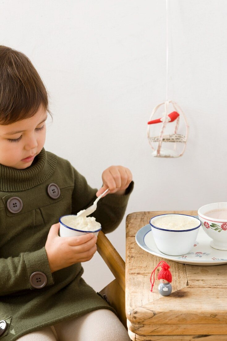 A young girl eating rice pudding