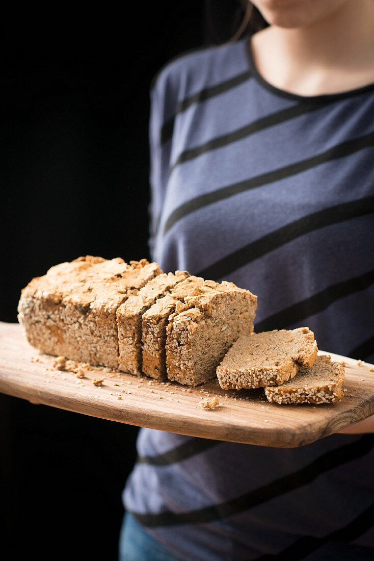 A loaf of seed bread on a wooden chopping board
