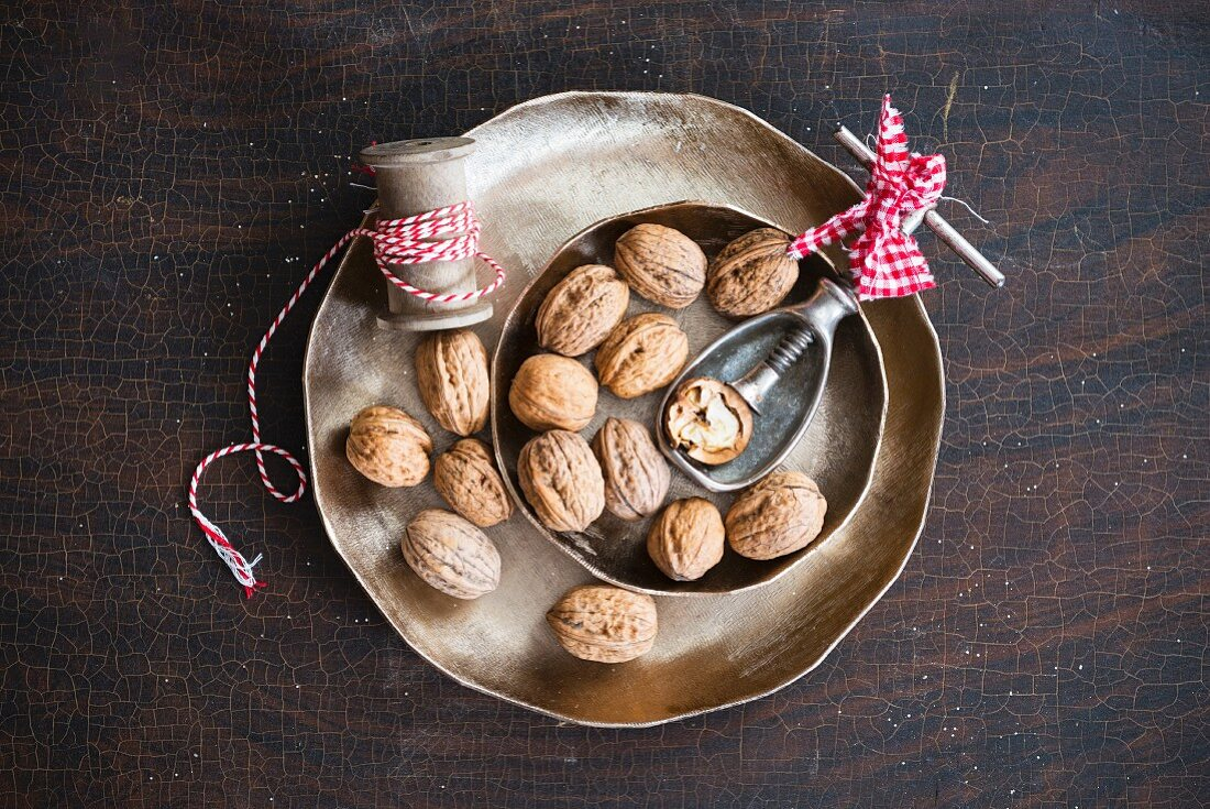 Walnuts with a nutcracker in a metal bowl