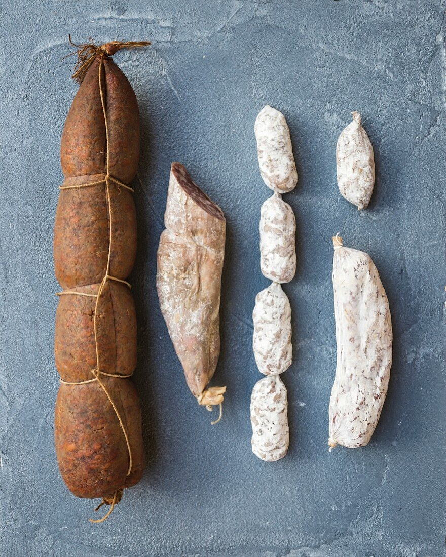 Italian salami sausages of different kinds over a rough grey-blue concrete background, top view
