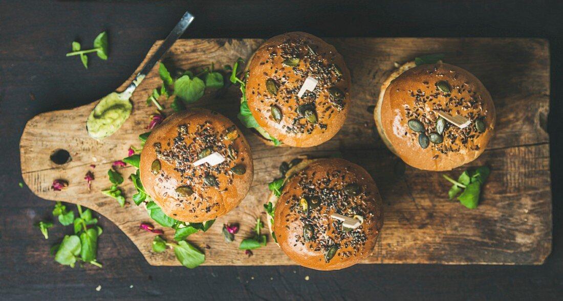Healthy vegan burger with beetroot and quinoa patty, arugula, avocado sauce, wholegrain bun on rustic wooden board