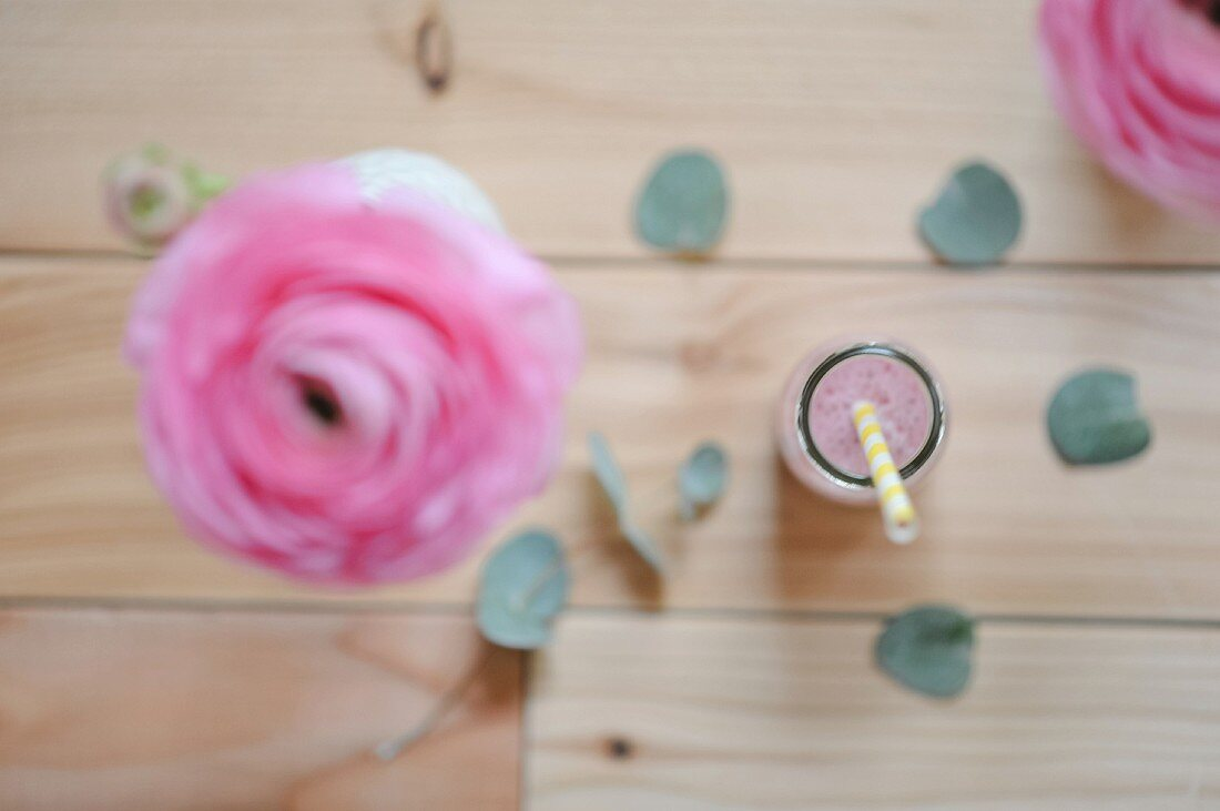 Raspberry milk with a straw in a bottle and a ranunculus flower in a vase (seen from above)