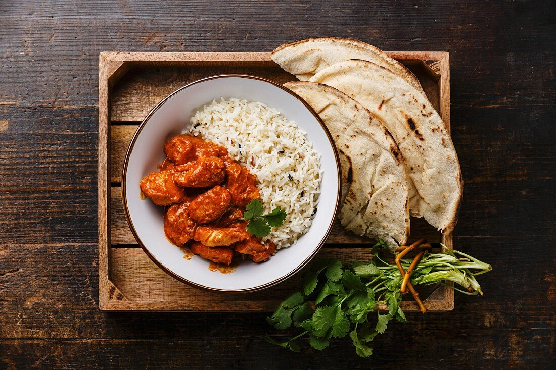 Chicken tikka masala spicy curry meat food in cast iron pot with rice and fresh naan bread