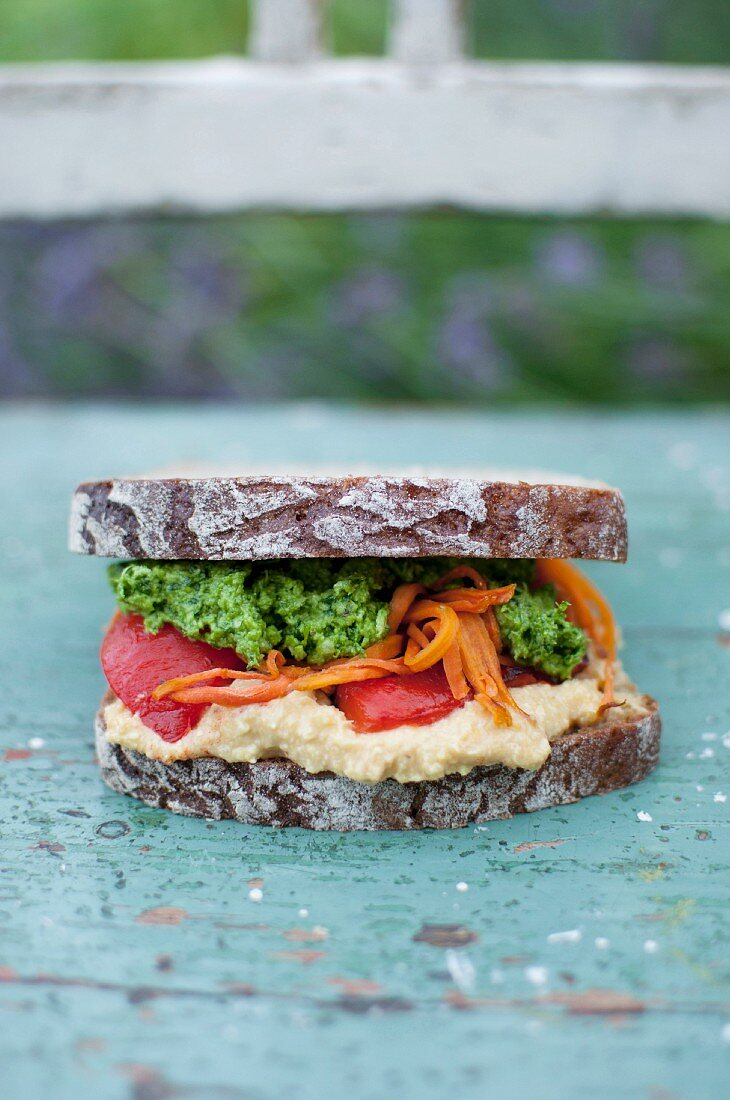 Vegan sandwich made from rye bread with corn hummus, roasted red pepper, carrot and parsley pesto
