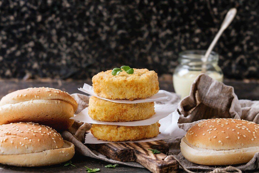 Ingredients for vegan burger. Veggie cheese and onion cutlets, yogurt sauce, hamburger buns and herb