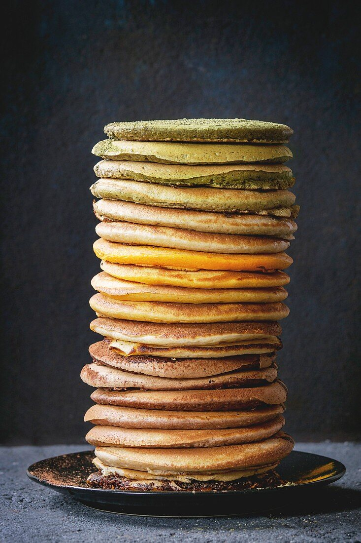 High stack of colorful homemade american ombre chocolate, green tea matcha and turmeric pancakes