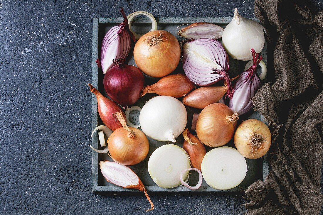 Variety of whole and sliced red, white, yellow and shallot onions on wooden square tray