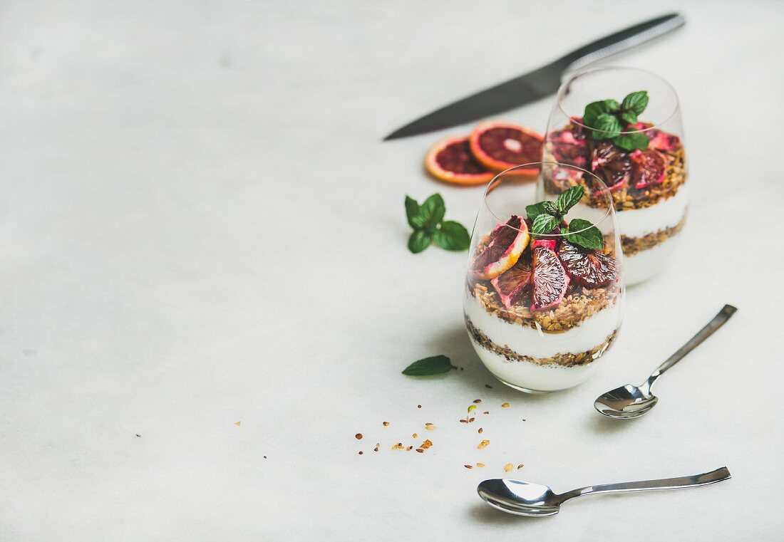 Healthy breakfast. Greek yogurt, granola and blood orange layered parfait in glasses with mint leaves