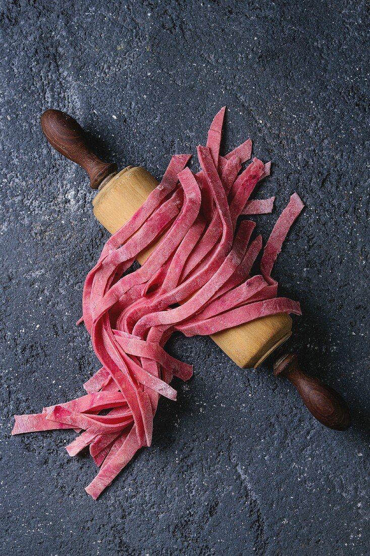 Frische selbstgemachte Rote-Bete-Tagliatelle auf Nudelholz (Aufsicht)