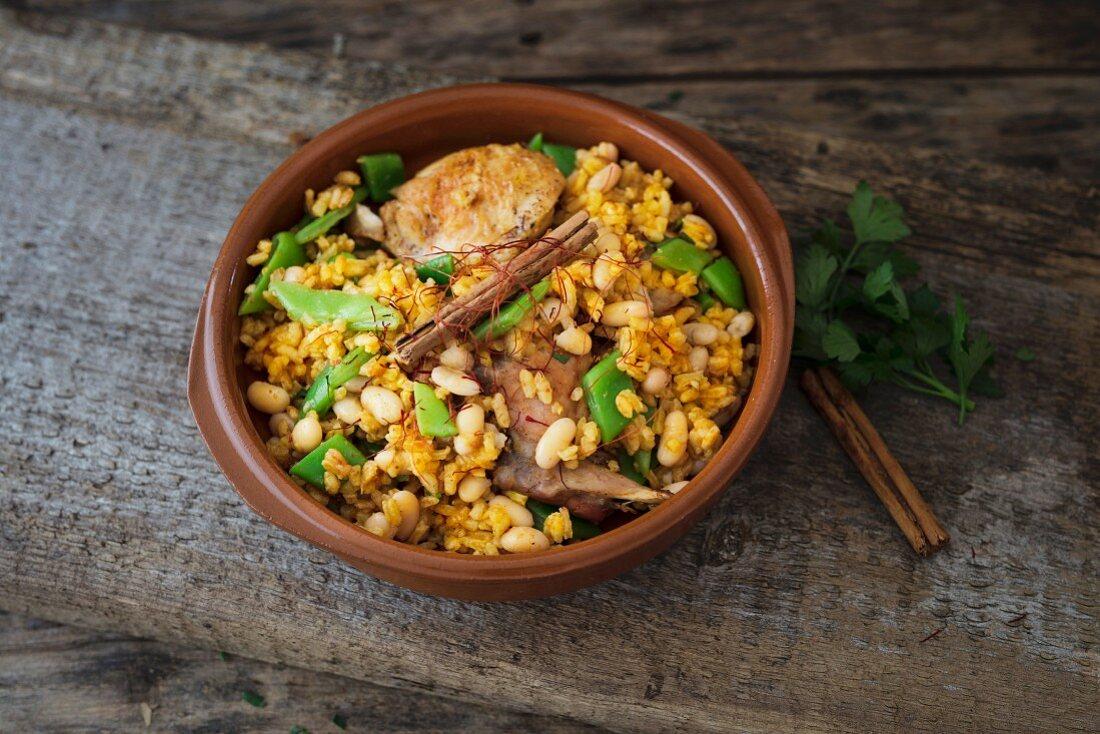 Paella Valenciana in a terracotta dish