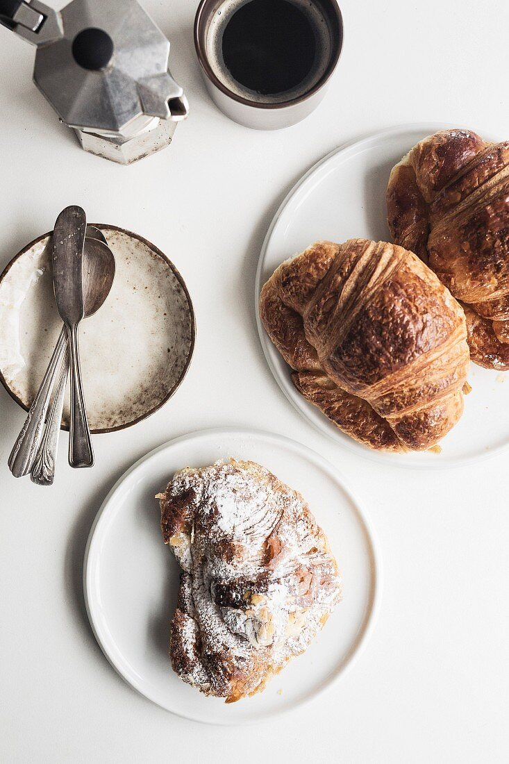 Two butter croissants, one almond croissant, one black coffee, a small plate with spoons and a butter knife arranged on a white tabletop