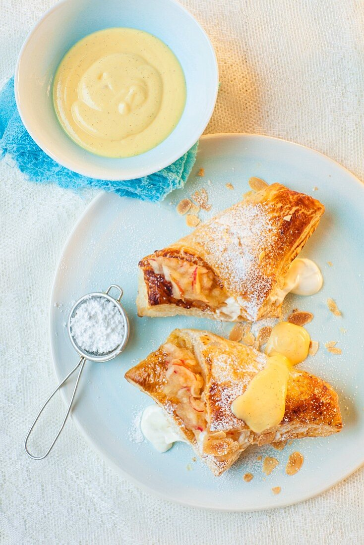 Apple and quark turnovers with icing sugar and custard
