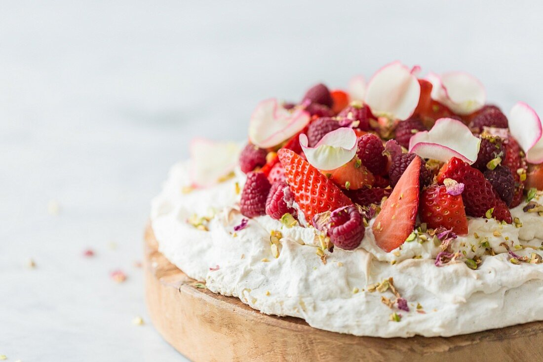 Rose and pistachio pavlova with fresh strawberries and raspberries, decorated with pistachio nuts and dried and fresh rose petals on a white and grey marble surface