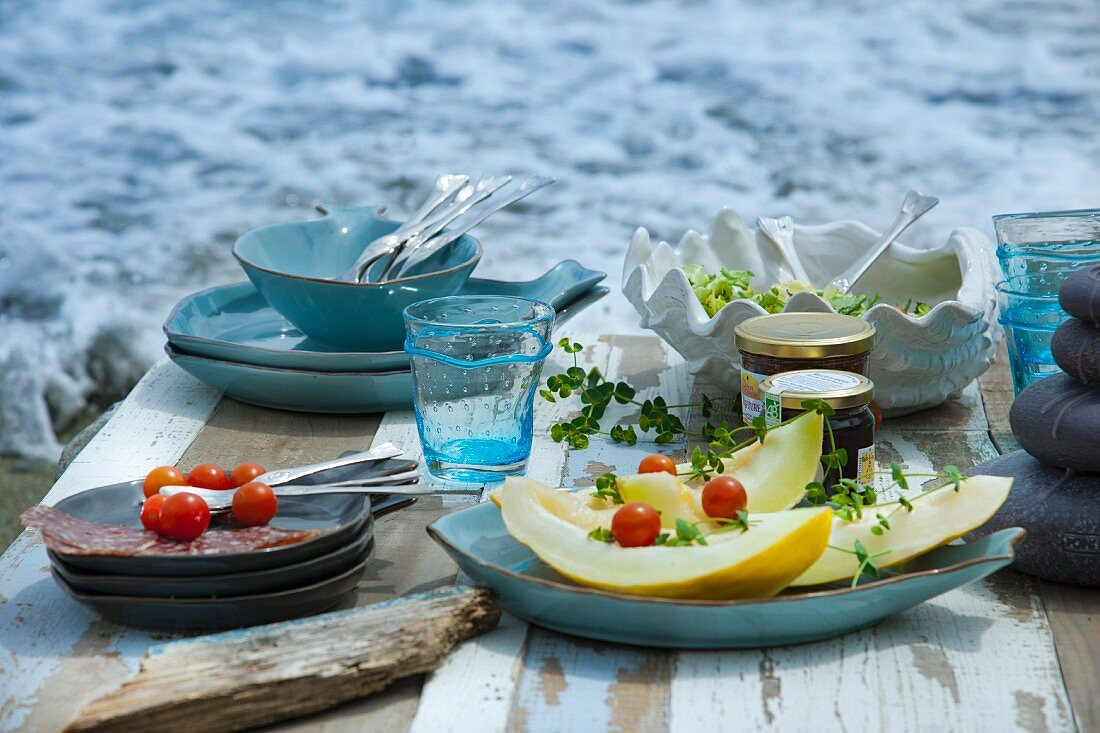 A picnic by the sea with melon, cherry tomatoes, salad, salami and fig chutney