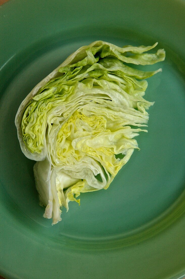 Iceberg lettuce on a green plate and green bacground