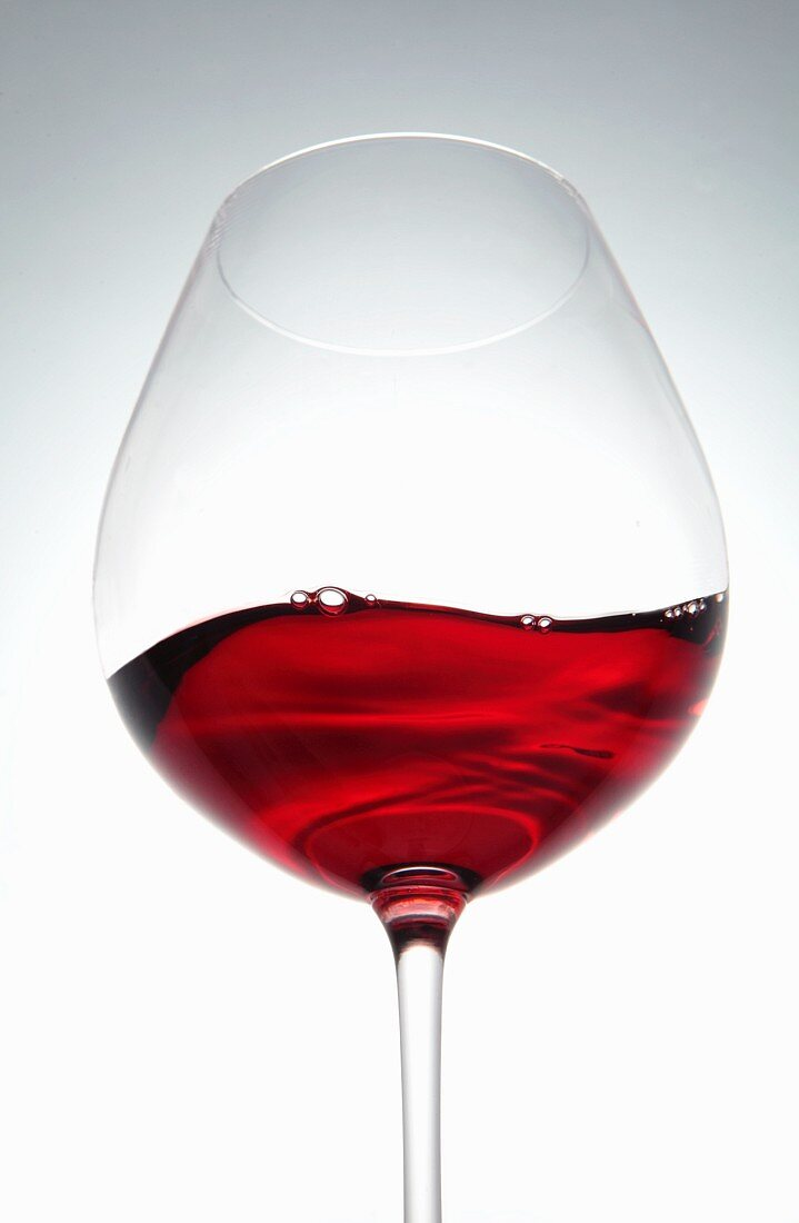 A wave of red wine in a glass