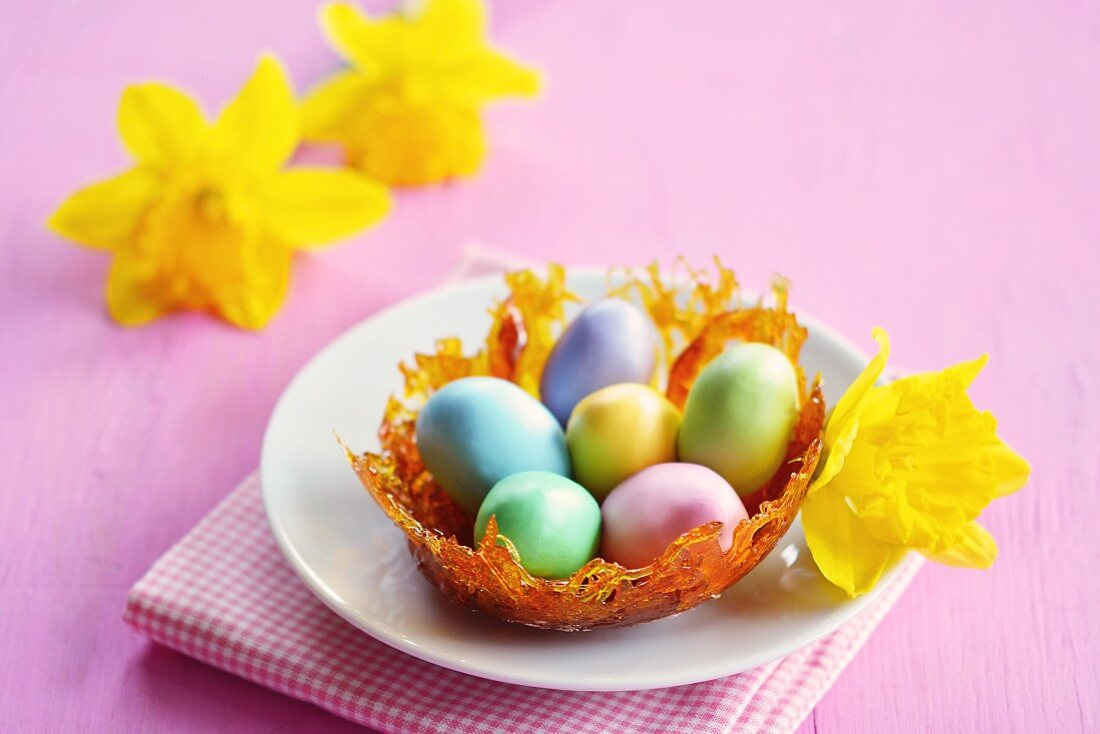 A caramel nest with colourful sugar eggs on a plate, and daffodils in the background