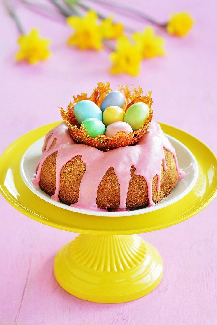 Gugelhupf mit rosa Zuckerguss und Zuckernest mit bunten Zuckereiern auf einer Etagere, im Hintergrund Osterglocken